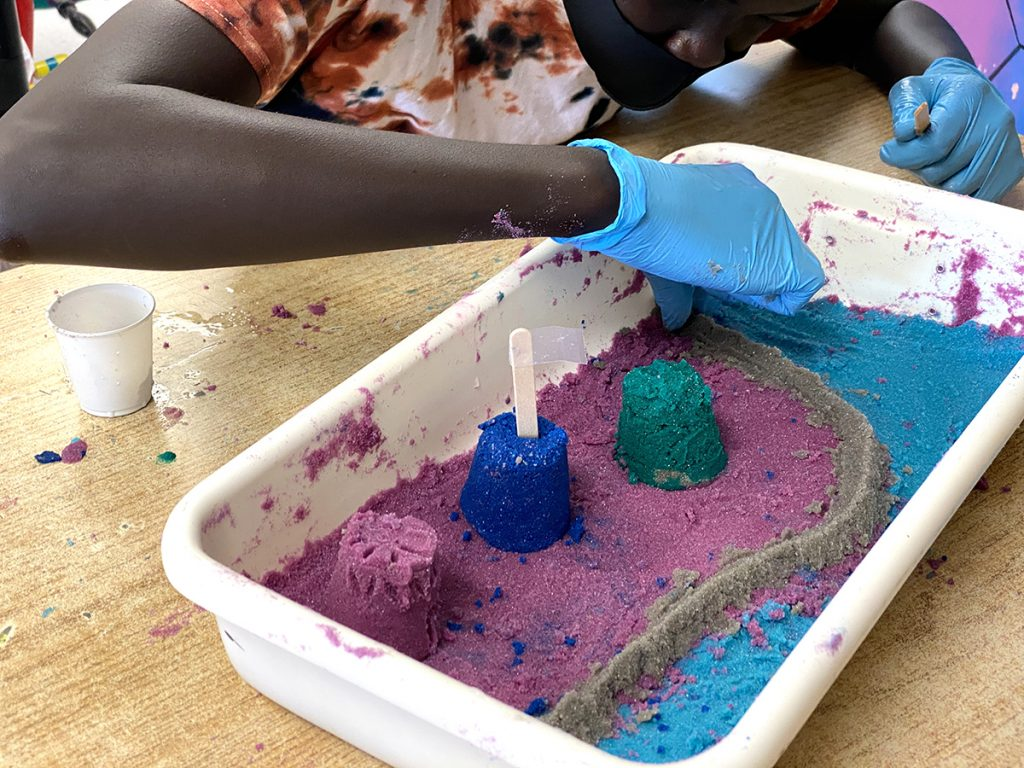 student creating sand art in plastic bin
